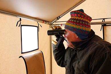 Tom Duffus watching the early spring mating ritual of the sharp-tailed grouse on their booming grounds. Photo by Ann Simonelli/The Conservation Fund.
